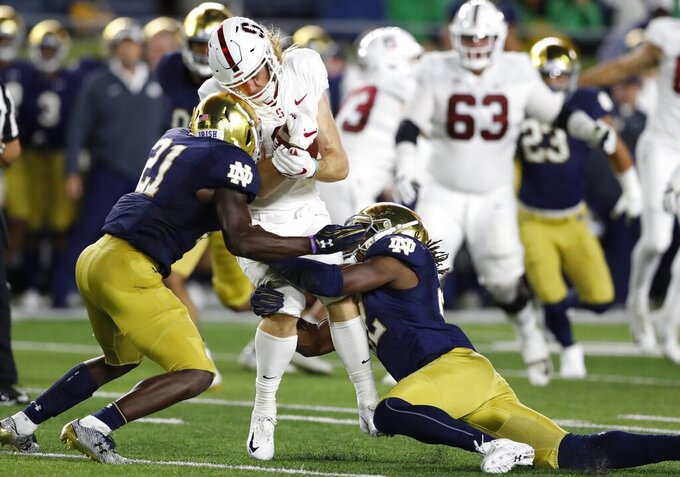 FILE - In this Sept. 29, 2018, file photo, Stanford wide receiver Trenton Irwin is stopped by Notre Dame safety Jalen Elliott (21) and linebacker Asmar Bilal during the first half of an NCAA college football game in South Bend, Ind. Notre Dame's second-year defensive coordinator Clark Lea has spent all spring, summer and preseason looking for replacements for graduated 2018 tackle leaders Te'von Coney and Drue Tranquill. In grad student Bilal and junior Drew White he may have found two of many. (AP Photo/Carlos Osorio, File)