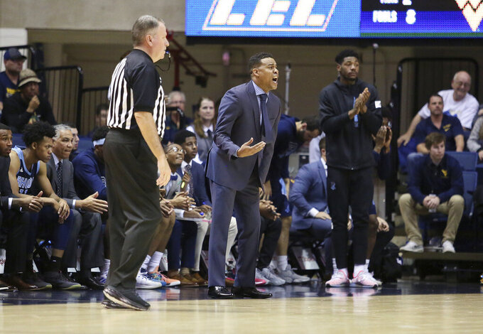 Rhode Island Coach David Cox, center, reacts during the second half against West Virginia during an NCAA college basketball game Sunday, Dec. 1, 2019, in Morgantown, W.Va. (AP Photo/Kathleen Batten)