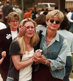 FILE - In this April 20, 1999, file photo, Fran Allison, right, comforts her daughter Brooke after they were reunited after a shooting at Columbine High School in Denver. Twelve students and one teacher were killed in a murderous rampage at the school on Tuesday, April 20, 1999, by two students who killed themselves in the aftermath. (AP Photo/Ed Andrieski, File)