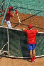 Philadelphia Phillies manager Joe Girardi, right, watches as J.T. Realmuto takes batting practice during a baseball training session, Friday, July 3, 2020, in Philadelphia. (AP Photo/Chris Szagola)
