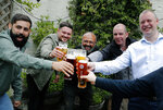 Men enjoy their first beers as the Chandos Arms pub reopens, in London, Saturday, July 4, 2020. England is embarking on perhaps its biggest lockdown easing yet as pubs and restaurants have the right to reopen for the first time in more than three months. In addition to the reopening of much of the hospitality sector, couples can tie the knot once again, while many of those who have had enough of their lockdown hair can finally get a trim. (AP Photo/Frank Augstein)