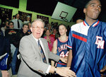 "FILE - In this Jan. 22, 1993, file photo, DeMatha High School basketball coach Morgan Wootten walks from the bench after his 1,000th victory, in Alexandria, Va. Next to Wootten are DeMatha players Tim Strachan (44) and Steve Napper, right. Morgan Wootten, a Hall of Fame basketball coach who built DeMatha High School into a national powerhouse and mentored several future NBA stars during a career that spanned parts of six decades, has died.  He was 88. The school announced his death on Twitter, writing, ""The Wootten Family is saddened to share the news that their loving husband and father Morgan Wootten passed away"