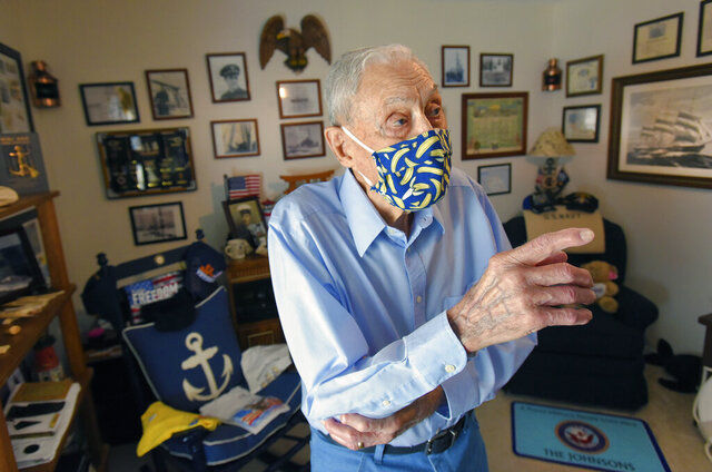 100 year old Bob Johnson gestures in the room of his home that contains photographs and mementos from his 20 year career in the U.S. Navy and his Antarctic explorations with Admiral Richard Byrd Tuesday, July 7, 2020 in Jacksonville, Fla. Robert Johnson, who turned 100 on Tuesday, a hot and sunny Florida day, barely hesitated when asked what he'd do if given another chance to go to Antarctica, the land of eternal ice and snow that he first journeyed to as a teenager. (Bob Self/The Florida Times-Union via AP)