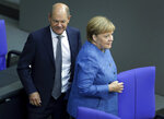 German Finance Minister Olaf Scholz left, and German Chancellor Angela Merkel, right, arrive for a meeting of the German federal parliament, Bundestag, at the Reichstag building in Berlin, Germany, Wednesday, Sept. 11, 2019. (AP Photo/Michael Sohn)