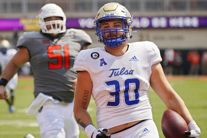 Tulsa linebacker Justin Wright (30) carries an interception into the end zone in the first half of an NCAA college football game against Oklahoma State, Saturday, Sept. 11, 2021, in Stillwater, Okla. (AP Photo/Sue Ogrocki)