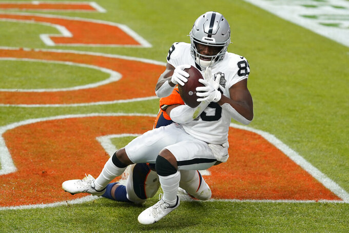 Las Vegas Raiders wide receiver Bryan Edwards (89) catches a pass for a touchdown over Denver Broncos cornerback Parnell Motley during the first half of an NFL football game, Sunday, Jan. 3, 2021, in Denver. (AP Photo/David Zalubowski)