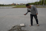 A man takes a picture of a hole at the Sanam Luang field in Bangkok, Thailand, Monday, Sept. 21, 2020. A plaque symbolizing Thailand's transition to democracy has been removed less than 24 hours after it was installed by anti-government demonstrators in a historic royal field. (AP Photo/Sakchai Lalit)