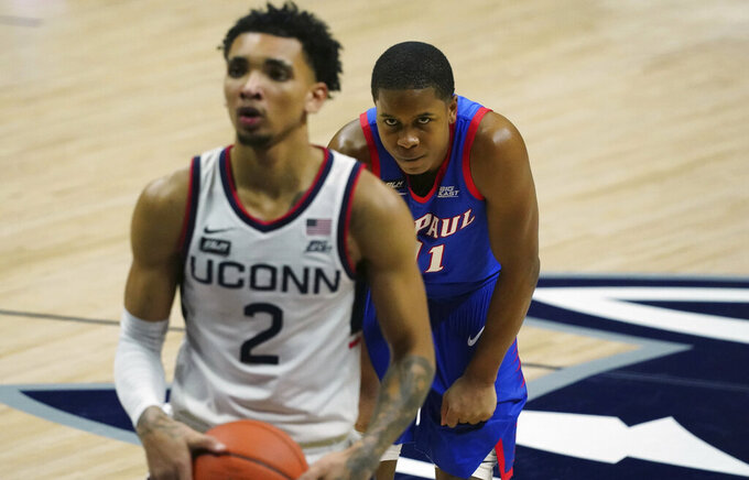 DePaul guard Charlie Moore (11) watches as Connecticut guard James Bouknight (2) prepares to shoot a free throw during the second half of an NCAA college basketball game Wednesday, Dec. 30, 2020, in Storrs, Conn. (David Butler II/Pool Photo via AP)