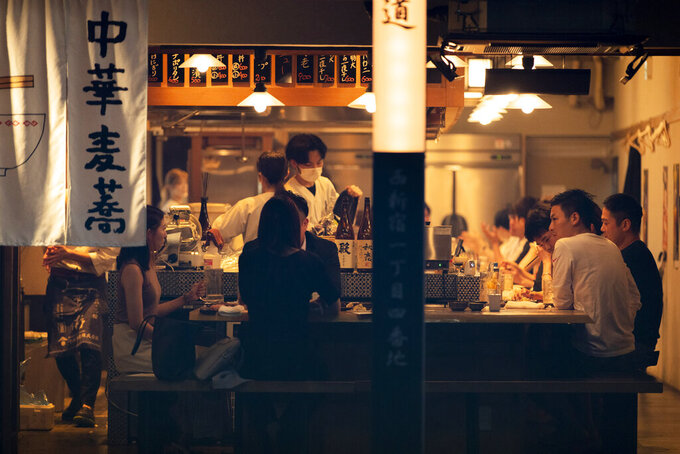 People eat and drink at a restaurant in the evening in Tokyo on July 9, 2021. A state of emergency began Monday, July 12, 2021, in Tokyo, as the number of new cases is climbing fast and hospital beds are starting to fill just 11 days ahead of the Tokyo Olympics. (AP Photo/Hiro Komae)