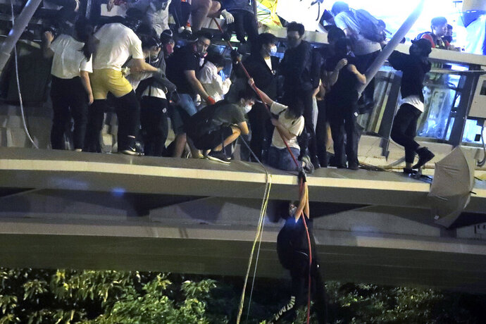Protestors use a rope to lower themselves from a pedestrian bridge to waiting motorbikes in order to escape from Hong Kong Polytechnic University and the police in Hong Kong, Monday, Nov. 18, 2019. As night fell in Hong Kong, police tightened a siege Monday at a university campus as hundreds of anti-government protesters trapped inside sought to escape. (AP Photo/Kin Cheung)