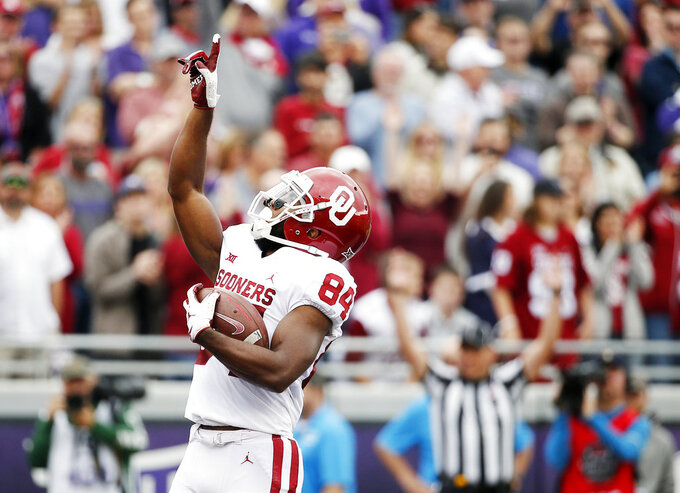 FILE - In this Saturday, Oct. 20, 2018, file photo, Oklahoma wide receiver Lee Morris (84) points skyward after scoring a touchdown during the first half of an NCAA college football game against TCU in Fort Worth, Texas. Oklahoma receiver Lee Morris and Oklahoma State quarterback Taylor Cornelius are among the top players in the nation who started their careers as walk-ons.  (AP Photo/Brandon Wade, File)