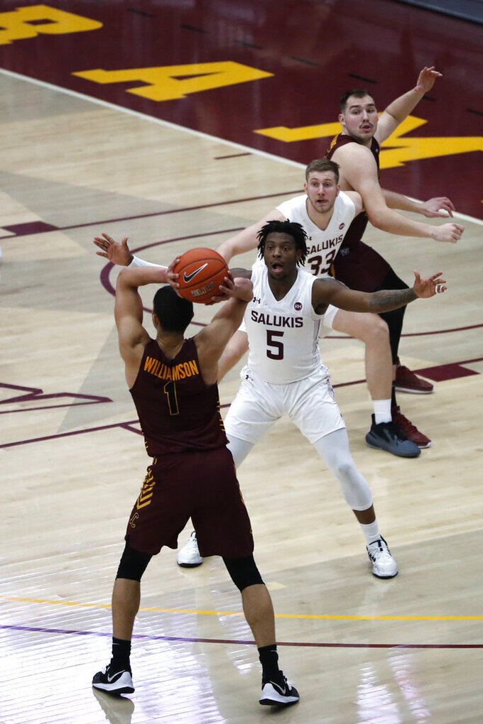 Loyola Chicago guard Lucas Williamson (1) aims to pass the ball as Southern Illinois' Lance Jones, front, and Anthony D'Avanzo, center, and Loyola Chicago's Cameron Krutwig watches during the first half of an NCAA college basketball game Saturday, Feb. 27, 2021, in Chicago. (AP Photo/Shafkat Anowar)