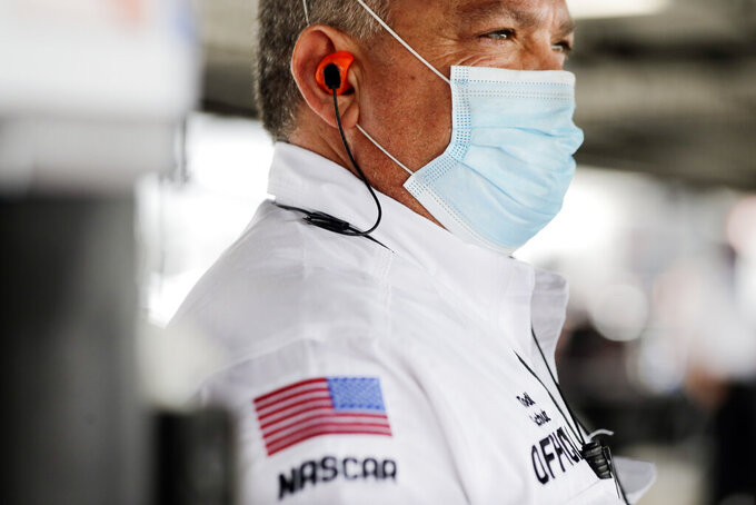 A NASCAR official wears a face mask because of the coronavirus pandemic as he works inside the garage before the NASCAR Xfinity series auto race Tuesday, May 19, 2020, in Darlington, S.C. NASCAR has developed a health plan approved by officials in both South Carolina and North Carolina and scheduled seven races over 11 days at two tracks. (AP Photo/Brynn Anderson)