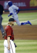 Arizona Diamondbacks starting pitcher Merrill Kelly, left, pauses on the mound after giving up a home run to Los Angeles Dodgers' Mookie Betts (50) during the fifth inning of a baseball game Sunday, Aug. 2, 2020, in Phoenix. (AP Photo/Ross D. Franklin)