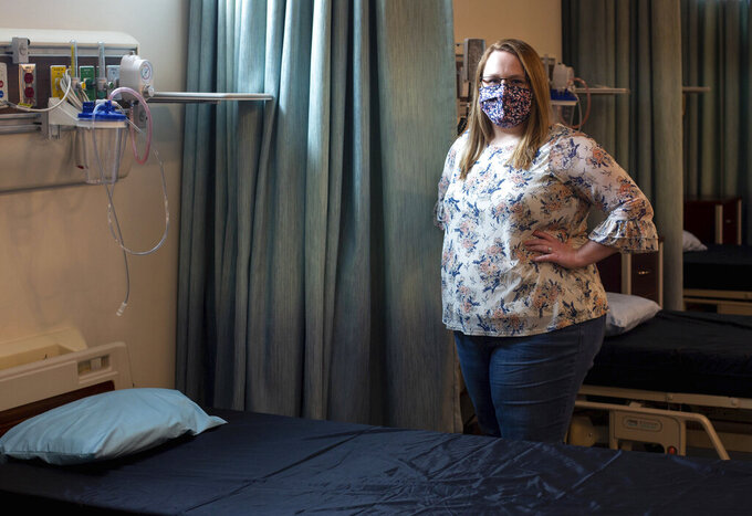 In this May 11, 2021 photo, Heather Fitzgerald, a recent Blue Ridge Community College nursing graduate, poses for a photo in a nursing lab in Weyers Cave, Va. (Daniel Lin/Daily News-Record via AP)