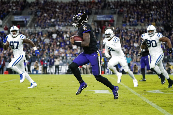 Baltimore Ravens quarterback Lamar Jackson (8) scrambles away from Indianapolis Colts defenders during the first half of an NFL football game, Monday, Oct. 11, 2021, in Baltimore. (AP Photo/Julio Cortez)