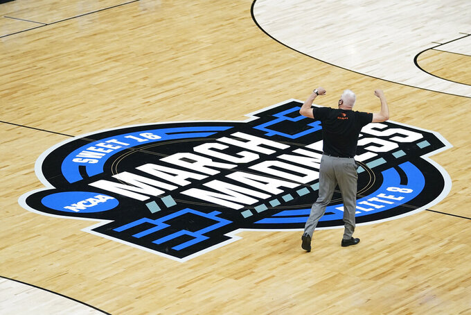 Oregon State head coach Wayne Tinkle celebrates as he walks off the court after a Sweet 16 game against Loyola Chicago in the NCAA men's college basketball tournament at Bankers Life Fieldhouse, Saturday, March 27, 2021, in Indianapolis. Oregon State won 65-58. (AP Photo/Darron Cummings)