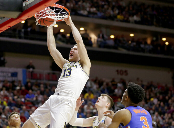 Michigan's Ignas Brazdeikis (13) dunks as Florida's Jalen Hudson (3) watches, during the first half of a second round men's college basketball game in the NCAA Tournament, in Des Moines, Iowa, Saturday, March 23, 2019. (AP Photo/Nati Harnik)