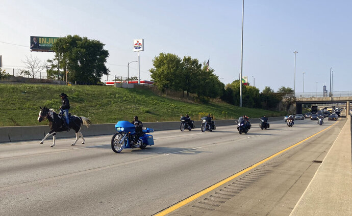 Adam Hollingsworth, the Dreadhead Cowboy, rides his horse down the local lanes of the Dan Ryan Expressway with motorcycles and motorists to support Kids Lives Matter, Monday, Sept. 21, 2020. (Todd Panagopoulos/Chicago Tribune via AP)