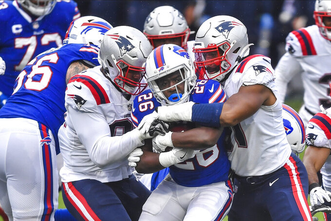 Buffalo Bills running back Devin Singletary (26) is tackled during the first half of an NFL football game against the New England Patriots Sunday, Nov. 1, 2020, in Orchard Park, N.Y. (AP Photo/Adrian Kraus)