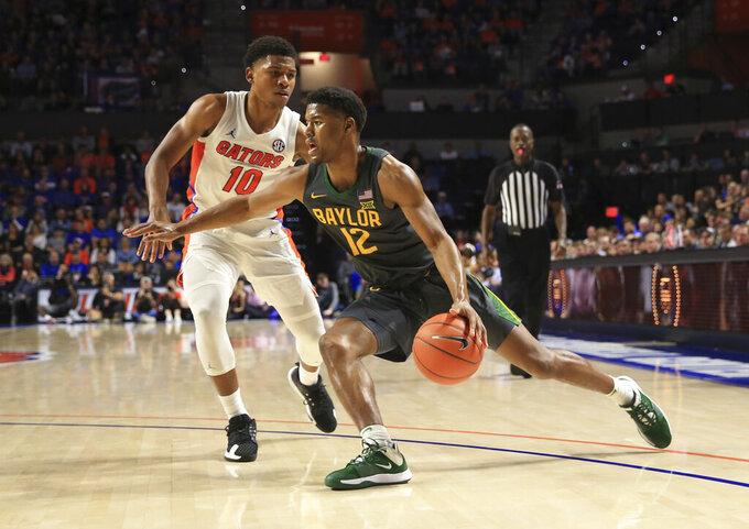 Baylor guard Jared Butler (12) drives around Florida guard Noah Locke (10) during the second half of an NCAA college basketball game Saturday, Jan. 25, 2020, in Gainesville, Fla. (AP Photo/Matt Stamey)