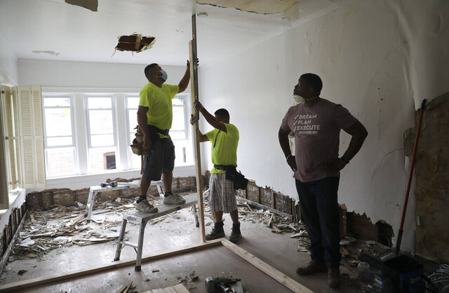 A construction crew working for Anton Downing, right, and his twin brother Anthony work on a bedroom of an apartment building that they are currently rehabbing in the south side, in Chicago, Saturday July 11, 2020. Chicago-area residents who have made a career out of flipping foreclosed or decrepit houses for a profit say the coronavirus pandemic that's hurt many businesses hasn't had much impact so far on house flipping. (Abel Uribe/Chicago Tribune via AP)