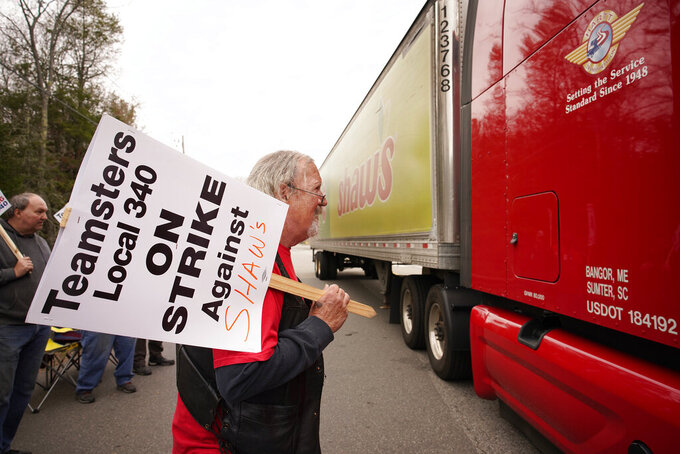 Jim Kelly, a truck driver with Shaw's supermarkets, looks at the driver of a truck leaving a Shaw's distribution facility while walking a picket line on strike, Monday, May 3, 2021, in Wells, Maine. Truck drivers for Shaw's supermarkets represented by the Teamsters went on strike Monday, May 3, stopping shipments to Shaw's and Star Market grocery stores in New England. (Gregory Rec/Portland Press Herald via AP)