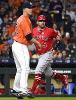 Los Angeles Angels' Albert Pujols (5) runs home to score on Andrelton Simmons' two-run double as Houston Astros starting pitcher Zack Greinke, left, watches during the fourth inning of a baseball game Friday, Sept. 20, 2019, in Houston. (AP Photo/Eric Christian Smith)