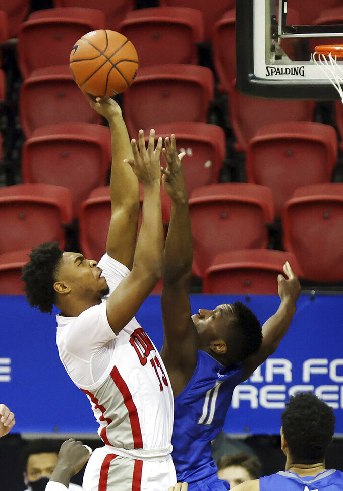 UNLV guard Bryce Hamilton (13) shoots as Air Force guard Ameka Akaya (11) defends during the first half of an NCAA college basketball game in the first round of the Mountain West Conference men's tournament Wednesday, March 10, 2021, in Las Vegas. (AP Photo/Isaac Brekken)