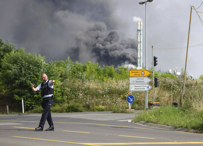 A police officer blocks an access road to the Chempark in Leverkusen, Germany, Tuesday, July 27, 2021 after an explosion in which the emergency services were in large-scale operation to tackle. (Oliver Berg/dpa via AP)
