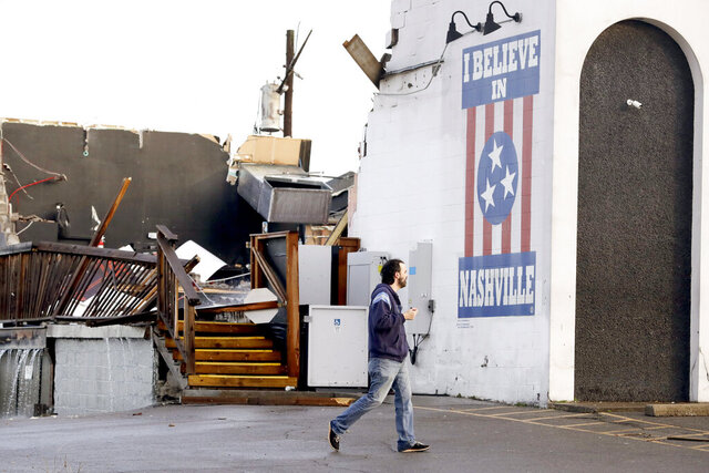 A man walks by The Basement East, a live music venue destroyed by storms Tuesday, March 3, 2020, in Nashville, Tenn.  Tornadoes ripped across Tennessee early Tuesday, shredding buildings and killing multiple people.  (AP Photo/Mark Humphrey)