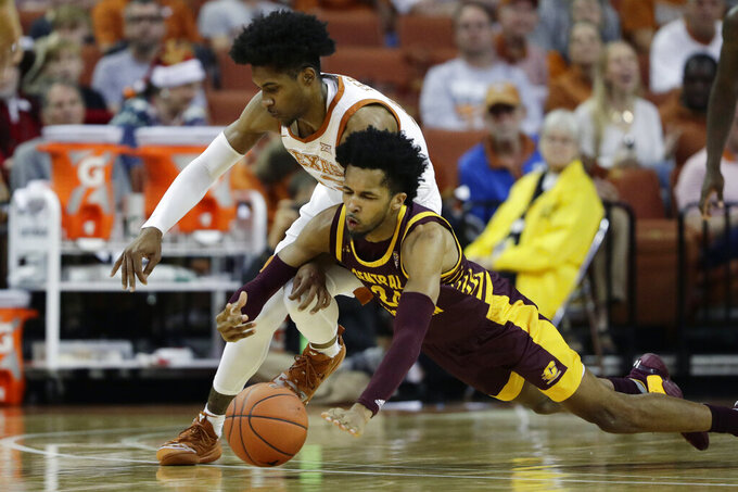Central Michigan forward Romelo Burrell (24) and Texas guard Jase Febres, left, chase a loose ball during the second half of an NCAA college basketball game, Saturday, Dec. 14, 2019, in Austin, Texas. (AP Photo/Eric Gay)