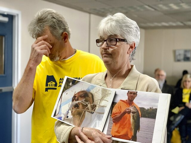 FILE - Sandy Ray, holds photos of her son, Steven Davis, during a news conference at the Alabama Statehouse in Montgomery on Dec. 4, 2019. The U.S. Department of Justice announced Thursday, July 23, 2020 that it believes Alabama's prisons for men are unconstitutional because inmates are subjected to excessive force at the hands of prison staff. (AP Photo/Kim Chandler, file)