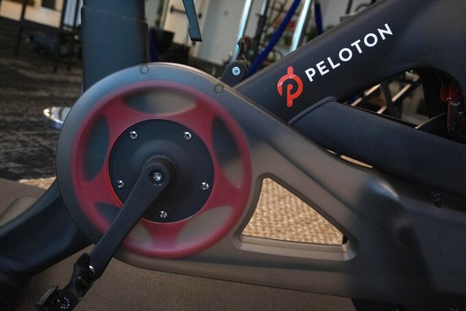 FILE - In this Sept. 26, 2019 file photo, the Peloton logo is displayed on the company's stationary bicycle in New York. Peloton plans to spend about $400 million to build its first U.S. factory in Ohio. The exercise equipment maker said Monday, May 24, 2021, that the Peloton Output Park will make the Peloton Bike, Bike+ and Peloton Tread starting in 2023. (AP Photo/Mark Lennihan, File)