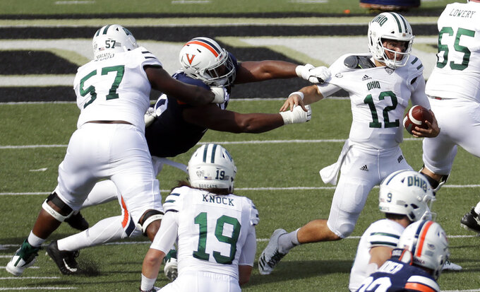 Ohio quarterback Nathan Rourke (12) escapes the grasp of Virginia defensive end Richard Burney, center, as Rourke scrambles for a 70-yard gain in the first half of an NCAA college football game Saturday, Sept. 15, 2018, in Nashville, Tenn. (AP Photo/Mark Humphrey)