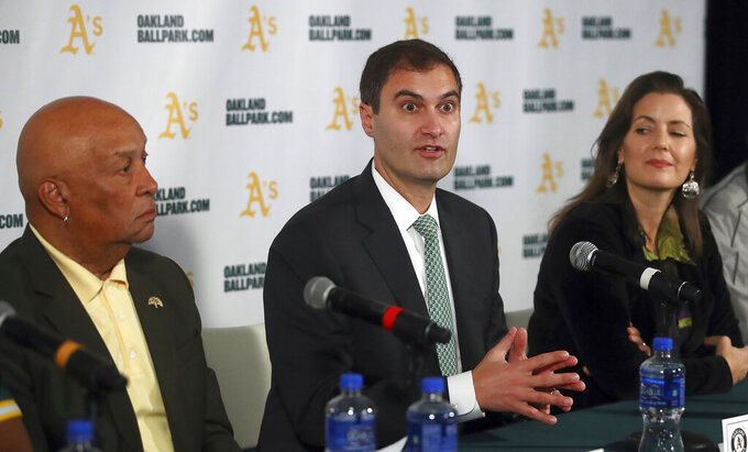 """FILE - Oakland Athletics President Dave Kaval, center, speaks beside Oakland Mayor Libby Schaaf, right, and Ces Butner, President of the Board of Port Commissioners, during a baseball news conference in Oakland, Calif., in this Wednesday, Nov. 28, 2018, file photo. Major League Baseball instructed the Athletics to explore relocation options as the team tries to secure a new ballpark it hopes will keep the club in Oakland in the long term. MLB released a statement Tuesday, May 11, 2021, expressing its longtime concern that the current Coliseum site is """"not a viable option for the future vision of baseball."""" (AP Photo/Ben Margot, FIle)"""