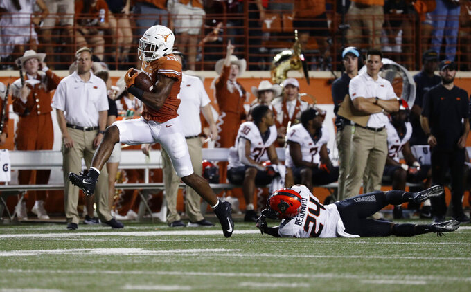 Texas wide receiver Brennan Eagles (13) high steps past Oklahoma State safety Jarrick Bernard (24) for a 73-yard touchdown during the first half of an NCAA college football game Saturday, Sept. 21, 2019, in Austin, Texas. (AP Photo/Eric Gay)