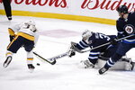 Winnipeg Jets goaltender Connor Hellebuyck (37) makes a save on Nashville Predators' Viktor Arvidsson (33) during first period NHL hockey action in Winnipeg, Manitoba, Sunday Jan. 12, 2020. (Fred Greenslade/The Canadian Press via AP)