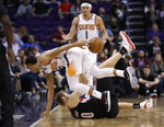 Phoenix Suns guard Elie Okobo, top front, passes around his back after chasing down a loose ball, over Portland Trail Blazers forward Jake Layman during the second half of an NBA basketball game Thursday, Jan. 24, 2019, in Phoenix. (AP Photo/Matt York)