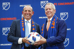 FILE - In this May 29, 2018, file photo, Major League Soccer commissioner Don Garber, left, and FC Cincinnati owner Carl Lindner III, right, pose for a photograph during an event to announce the addition of FC Cincinnati as an MLS expansion team at Rhinegeist Brewery in Cincinnati. Cincinnati joins MLS as the league's 24th team. The club is coming off a tremendous season in the USL, finishing with a 28-8-3 record to claim the league's regular-season title. (AP Photo/John Minchillo)