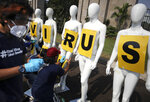 Greenpeace activists attach posters on mannequins displayed during a protest outside the parliament, amid the new coronavirus outbreak in Jakarta, Indonesia, Monday, June 29, 2020. About a dozen of activists staged the protest against the government's omnibus bill on job creation, saying that it undermined labor rights and environmental protection, and called on the parliament members to focus their attentions on efforts to contain COVID-19 outbreak instead. (AP Photo/Dita Alangkara)