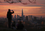 A person takes a photo of the skyline with the Shard building in the center, at sunset, from Greenwich Park in London, Tuesday, Nov. 24, 2020. (Yui Mok/PA via AP)