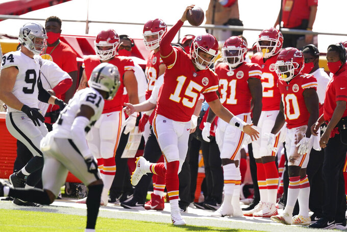 Kansas City Chiefs quarterback Patrick Mahomes (15) runs from Las Vegas Raiders cornerback Amik Robertson (21) during the first half of an NFL football game, Sunday, Oct. 11, 2020, in Kansas City. (AP Photo/Charlie Riedel)