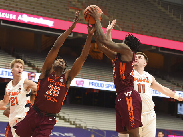 Virginia Tech forward Justyn Mutts (25) and guard Tyrece Radford (23) reach for a rebound against Syracuse's Joseph Girard (11) and Marek Dolezaj (21)  during an NCAA college basketball game at the Carrier Dome, Syracuse, N.Y., Saturday Jan. 23, 2021. (Scott Schild/The Post-Standard via AP)