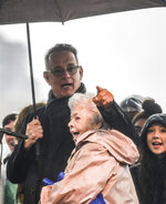 Actor Tom Hanks embraces Joanne Rogers, the late wife of Fred Rogers, as they sing the theme song of