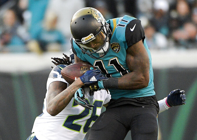 FILE - In this Dec. 10, 2017, file photo, Jacksonville Jaguars wide receiver Marqise Lee (11) makes a reception in front of Seattle Seahawks cornerback Shaquill Griffin during the first half of an NFL football game in Jacksonville, Fla. Lee is practicing for the first time since tearing three ligaments in his left knee last preseason. (AP Photo/Phelan M. Ebenhack, File)