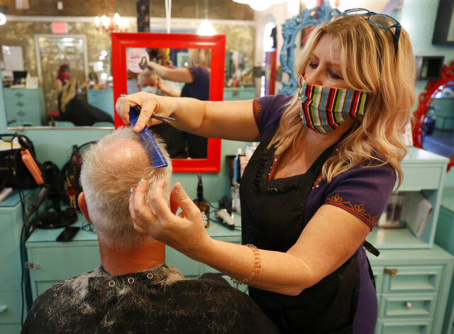 Michelle Harris gives a client a haircut at Rockabetty's Hair Parlor, in Yuba City, Calif., Monday, May 4, 2020. Monday was the first day businesses could open in Sutter County under a modified public health order. (AP Photo/Rich Pedroncelli)