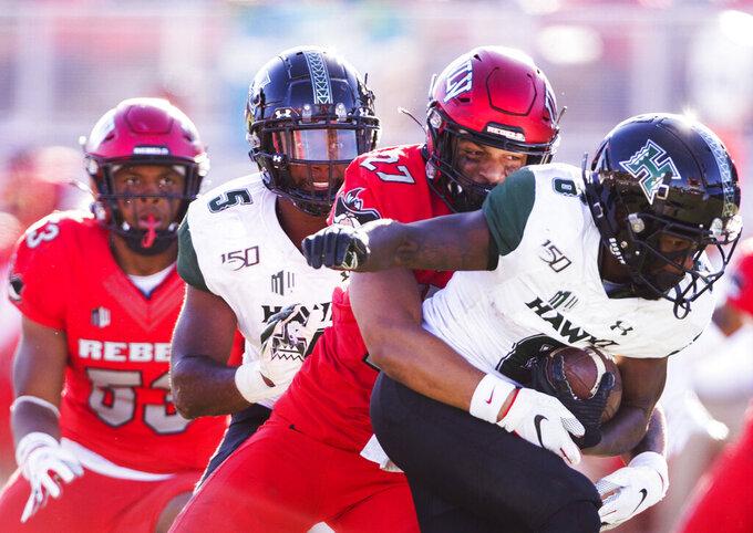 UNLV linebacker Austin Ajiake (27) tackles Hawaii wide receiver Cedric Byrd II (6) in the second quarter of an NCAA college football game Saturday, Nov. 16, 2019, in Las Vegas. (Benjamin Hager/Las Vegas Review-Journal via AP)
