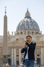 Mathieu De La Souchere speaks on his cellphone after an interview with The Associated Press in St. Peter's Square at The Vatican, Wednesday, July 3, 2019. One of the half-dozen men who have accused the Vatican's ambassador to France of groping them is taking his complaint directly to the Vatican after claiming the Holy See had invoked diplomatic immunity in a French criminal probe. Mathieu De La Souchere met with one of Pope Francis' sex abuse advisers on Wednesday after filing a police report in Paris earlier this year. (AP Photo/Domenico Stinellis)