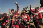 Driver Carlos Sainz, of Spain, center, is lifted by Driver StÈphane Peterhansel, of France, center and left, and driver Nasser Al-Attiyah, of Qatar, center and right, at the end of stage twelve of the Dakar Rally between Haradth and Qiddiya, Saudi Arabia, Friday, Jan. 17, 2020. (AP Photo/Bernat Armangue)